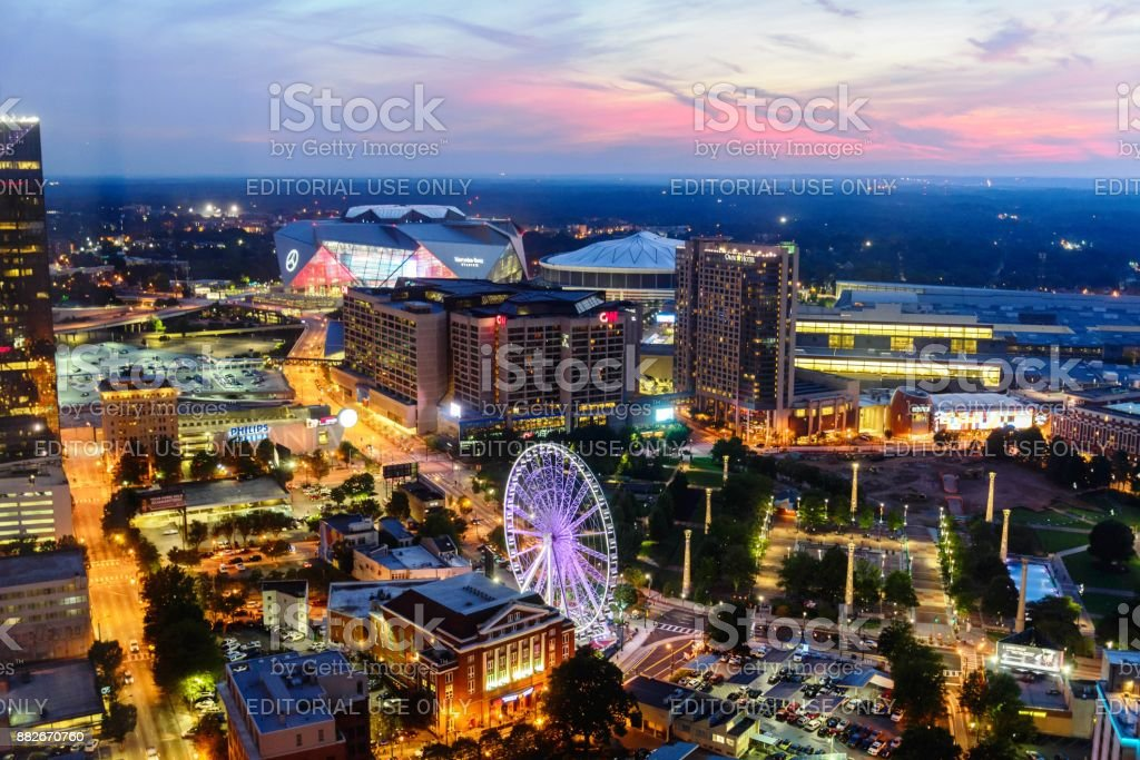 downtown cityscape of Atlanta, Georgia,  Centennial Park, August 22, 2017 downtown high elevation dusk view of Atlanta, Georgia,  Centennial Park, August 22, 2017, after the sun has gone down with a lighted Ferris wheel and pink sky 2017 Stock Photo