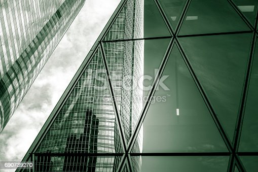 istock Downtown corporate business district architecture, glass reflective office buildings with green tone 690739270