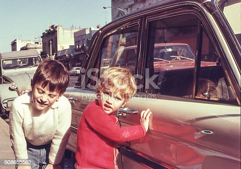 photo from the seventies of two children next to a car in the street.