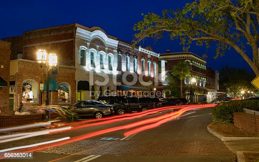 Downtown stores in the small town of Fernandina Beach are lit against the evening sky by ribbons of traffic light.