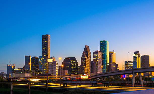 downtown houston skyline at sunset with orange reflection - houston texas stock-fotos und bilder