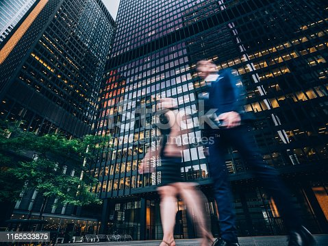 Two business people walking on downtown street. Blurred motion effect.
