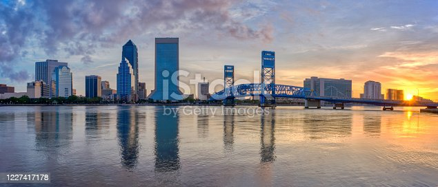 The downtown skyline of Jacksonville, Florida during sunrise.  The view is from the Southbank Riverwalk area and features the St. Johns River and the John T. Alsop Jr. Bridge.