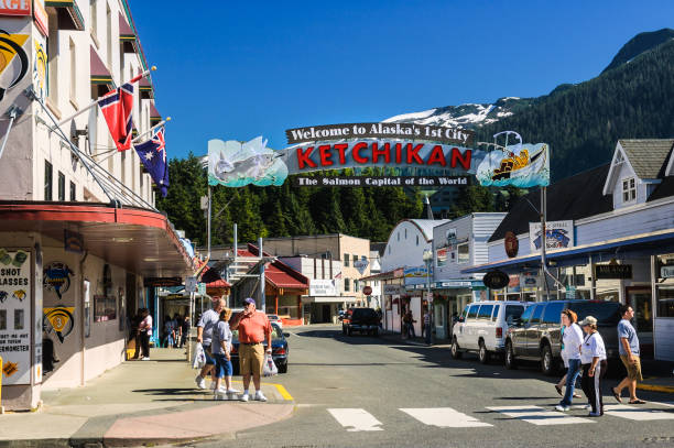 Downtown Ketchikan Ketchikan, Alaska, USA - August 15, 2007: Tourists visit  the many shops on Front  Street in  Ketchikan, Alaska beneath a city welcome sign ketchikan stock pictures, royalty-free photos & images