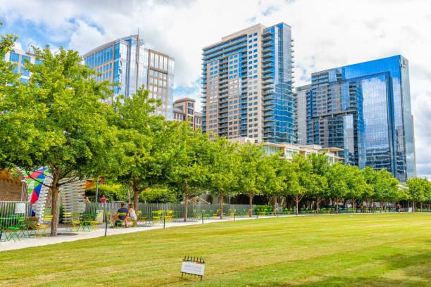 Parque verde de Klyde Warren do centro no verão com grama do gramado e Skyline da arquitectura da cidade - foto de acervo