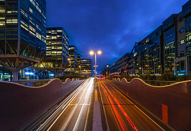 Downtown Leiden Rush hour in a busy city in the early morning. Cars passing by leaving light trails inbetween the modern Architecture. leiden stock pictures, royalty-free photos & images