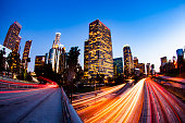 Traffic flows through a busy downtown Los Angeles at twilight after the sun has set.