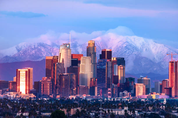 Downtown Los Angeles skyline with snow capped mountains behind at sunset stock photo