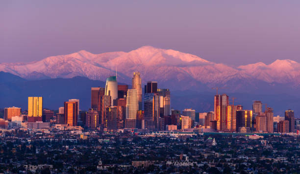 Downtown Los Angeles skyline with snow capped mountains behind at twilight stock photo