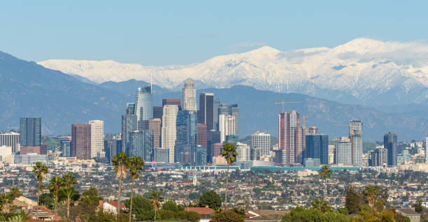 Downtown Los Angeles skyline with snow capped mountains behind at sunny day stock photo