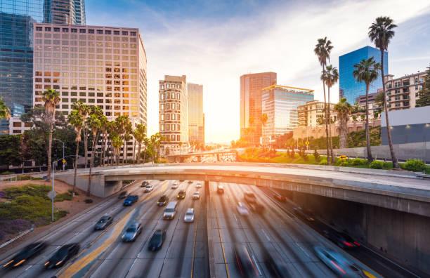 движение в центре лос-анджелеса на закате - деловой центр города стоковые фото и изображения