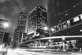 This is a horizontal, black and white, royalty free stock photograph of downtown Miami city buildings at dusk. Traffic passes in streaks of light along Biscayne Blvd.  Photographed with a Nikon D800 DSLR camera.