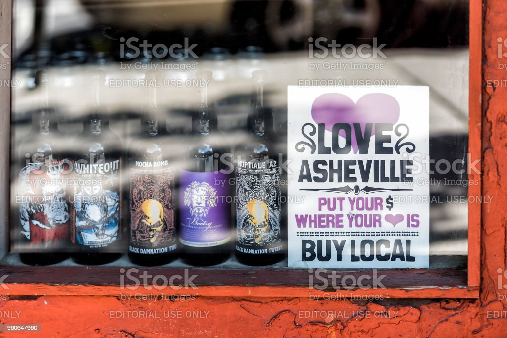 Downtown old town street in hipster North Carolina NC famous town, city with storefront store, shop, nobody display of local beer, sign stock photo