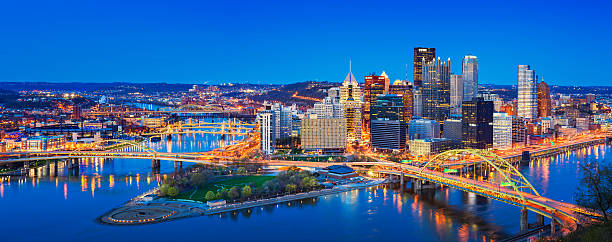 Downtown Pittsburgh Pennsylvania USA Panoramic cityscape photo of downtown Pittsburgh, Pennsylvania, USA, illuminated at twilight blue hour. It is located at the confluence of the Allegheny and Monongahela rivers. pittsburgh stock pictures, royalty-free photos & images