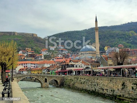 Old stone bridge over a small river and a mosque in the background in the city of Prizren in Kosovo March 26,2016