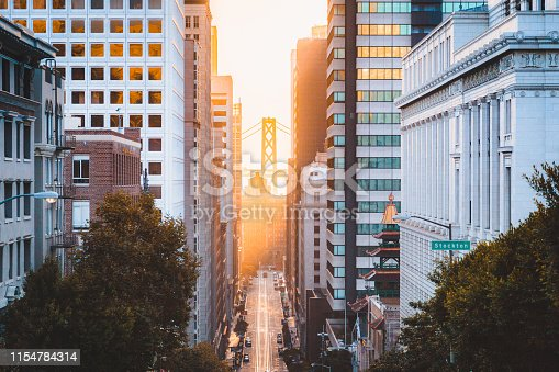 Beautiful view of downtown San Francisco with famous California Street illuminated in first golden morning light at sunrise in summer, San Francisco, California, USA