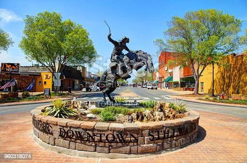 Stillwater, Oklahoma, USA - April 24, 2018: Daytime view of the enlarged bronze replica of 'The Bronco Buster' by famed sculptor Frederic Remington in a roundabout on Main Street in Stillwater Oklahoma