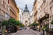 Budapest, Hungary - july 9, 2018. Street leading to neoclassical St. Stephen's Basilica - popular landmark, largest church in Budapest. Downtown pedestrian street with trees, cafes and restaurants.