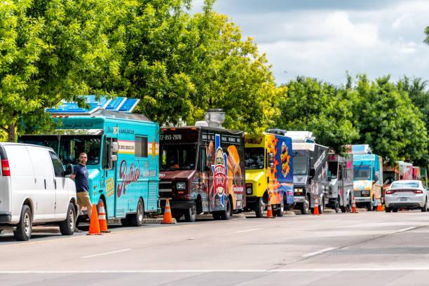 Rua da baixa pelo parque de Klyde Warren com muitos caminhões de alimento coloridos para o BBQ de Texas - foto de acervo