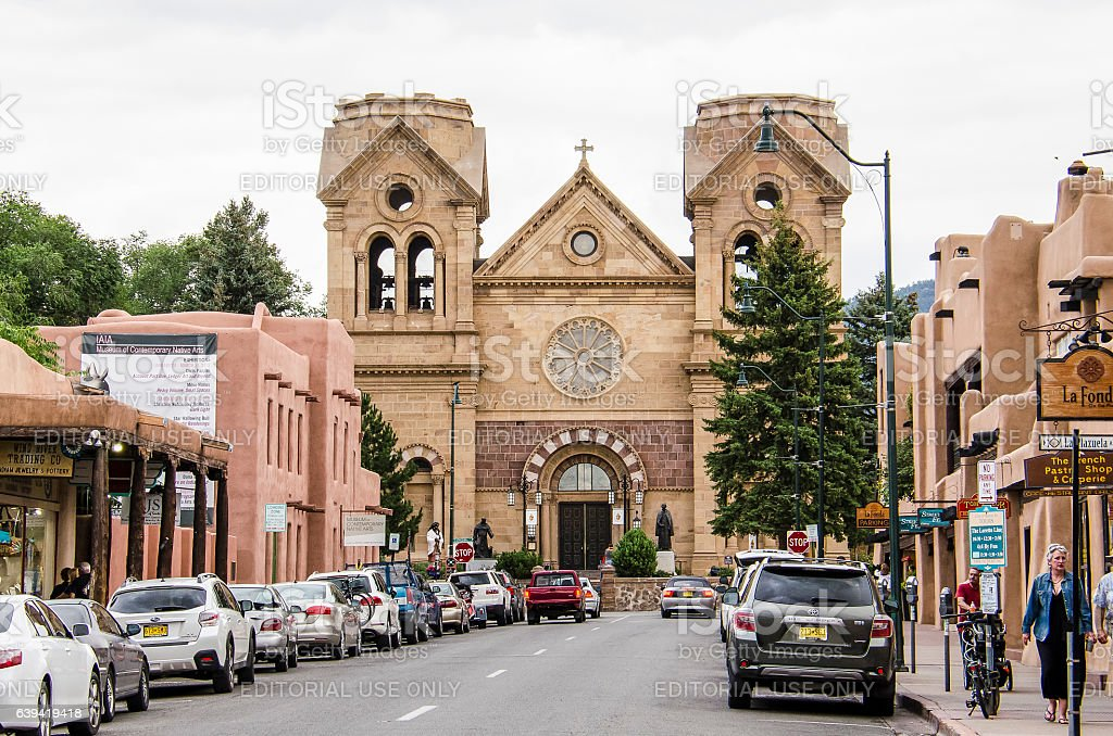 Downtown street with Cathedral Basilica of St. Francis of Assisi Santa Fe, United States - July 29, 2015: Downtown city street with parked cars and Cathedral Basilica of St. Francis of Assisi in New Mexico Adobe - Material Stock Photo