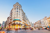 Wide angle stock photograph of pedestrians crossing street in downtown Valencia, Spain with ornate apartment houses in the backround