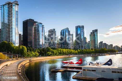Photo of Vancouver Waterfront at Sunset with High Rise Glass Buildings Lit by Warm Sunlight. Two Moored Seaplanes are in Foreground. Vancouver, BC, Canada.