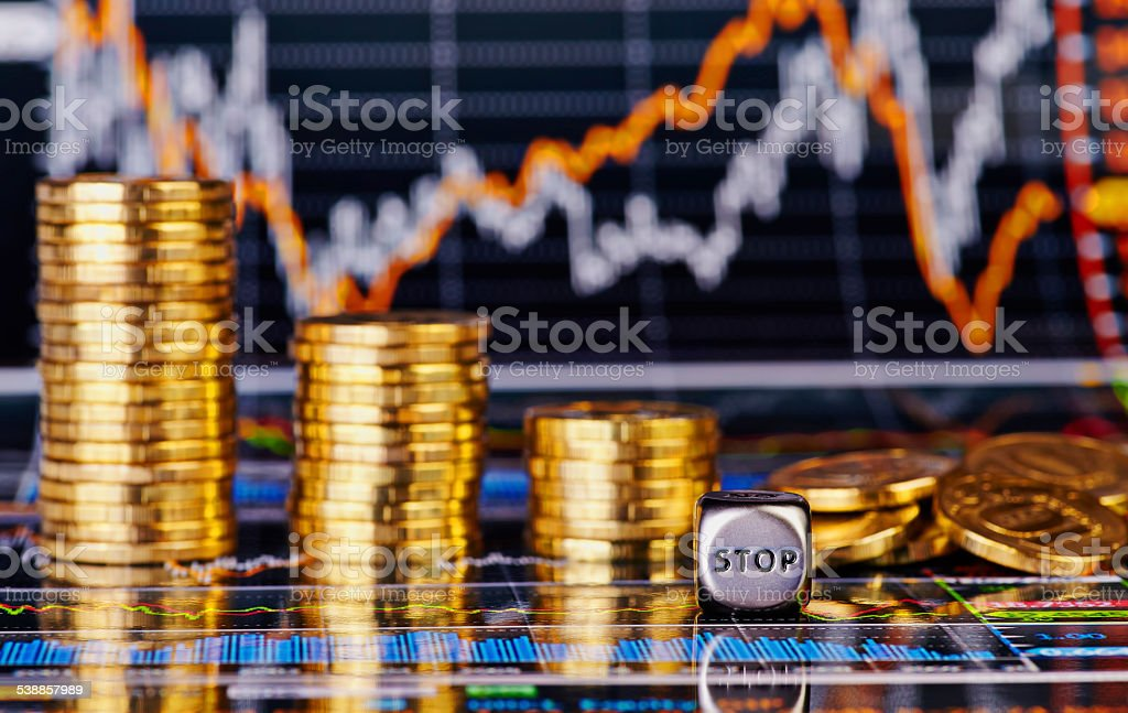 Downtrend golden coins stacks, dices cube with the word STOP stock photo