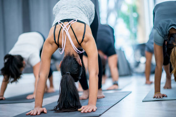 Downward Dog A multi-ethnic group of men and women are at a health center. They are doing yoga together. Here they are doing the downward dog pose. yoga studio stock pictures, royalty-free photos & images