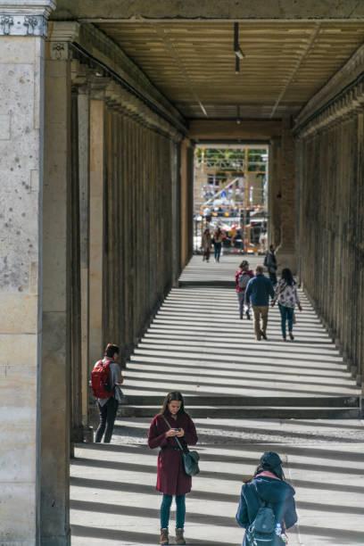 Abwärts und tiefgründige Perspektive der Berliner, die unter einem Bau auf der Museumsinsel, einem Museumskomplex neben dem Berliner Dom, spazieren gehen – Foto