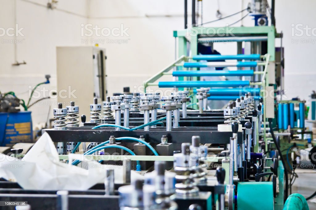 doypack making packaging machine in modern factory with white walls...