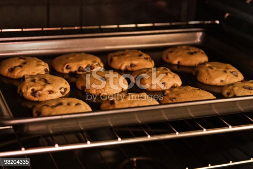 Chocolate chip cookies baking on the oven rack.