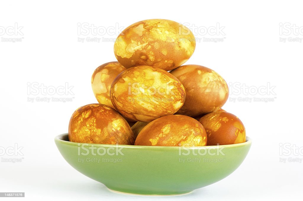 Dozen golden marbled Easter eggs in green bowl royalty-free stock photo
