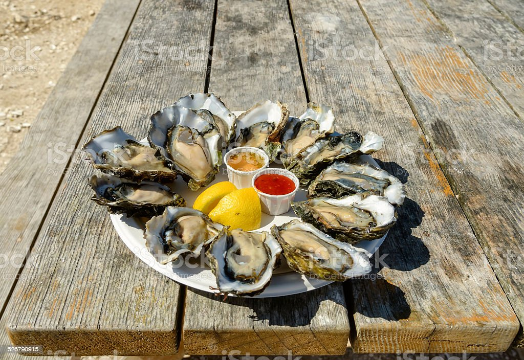 Dozen of oysters with lemon and sauce in a plate. stock photo