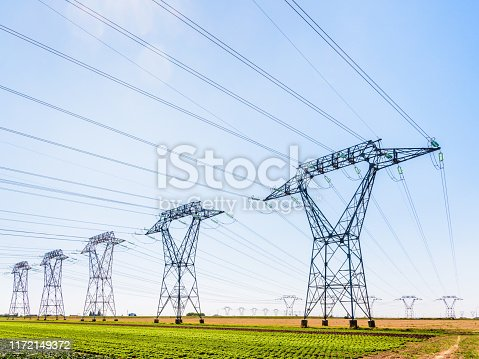 Dozens of electricity pylons in the french countryside under a clear blue sky.