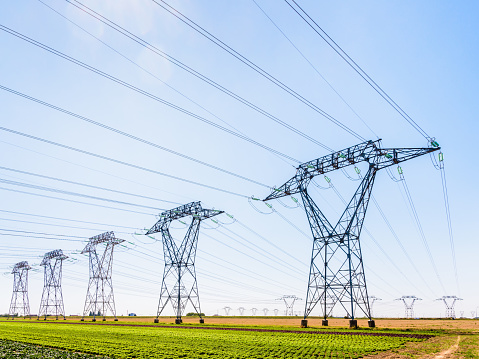 Dozens of electricity pylons in the countryside under a clear blue sky.