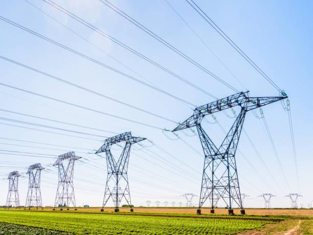 Des dizaines de pylônes électriques dans la campagne sous un ciel bleu clair. - Photo