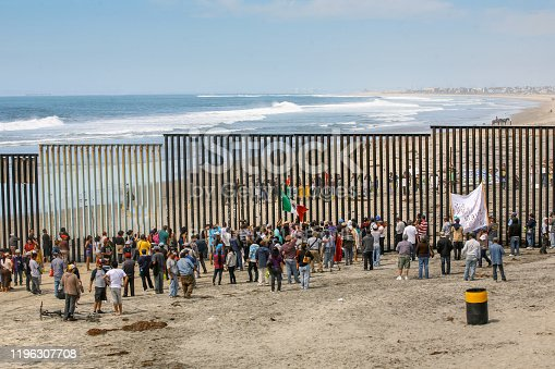 Tijuana, Mexico, March 29 - Migrants and workers gather on both sides of the iron and steel wall that separates the border between Mexico and the United States in Playas de Tijuana.