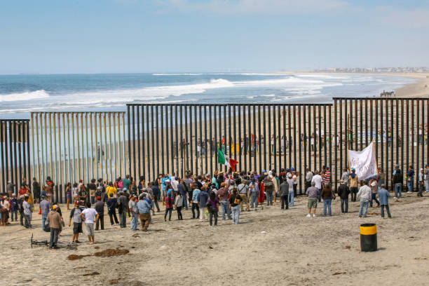 Migrants and workers on the border between Mexico and US Tijuana, Mexico, March 29 - Migrants and workers gather on both sides of the iron and steel wall that separates the border between Mexico and the United States in Playas de Tijuana. frontier field stock pictures, royalty-free photos & images