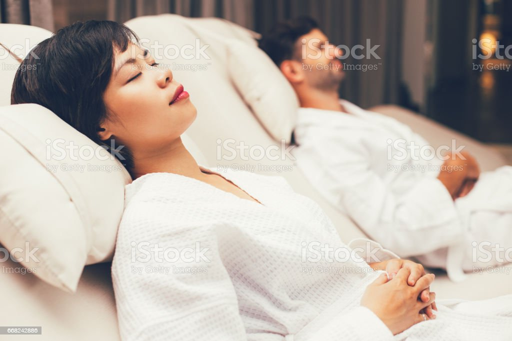 Dozing woman and man lying on deckchairs in spa stock photo