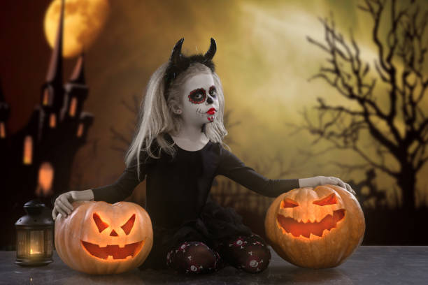 dracula child.little mädchen mit halloween make-up. das bild des teufels mit hörnern - dracula schminken stock-fotos und bilder