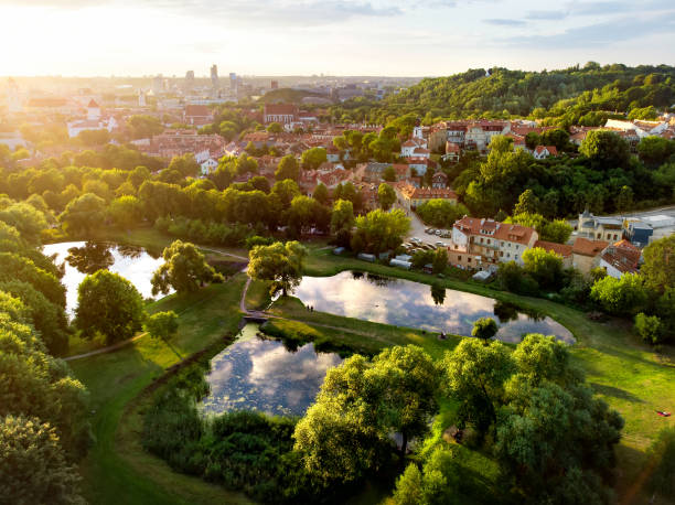 drAerial view of Vilnius cityscape shot from Subaciaus viewpoint on sunset. Clouds reflecting in three ponds of Lithuania capital's city park. stock photo