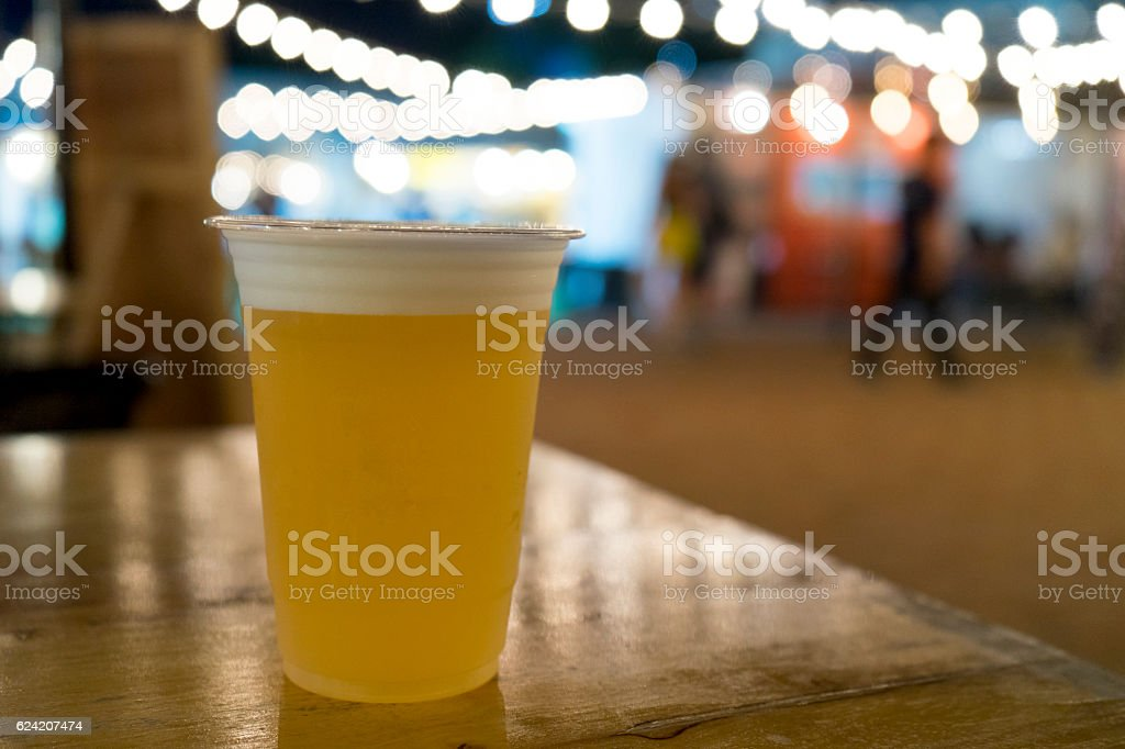 draft beer in plastic cup on wooden table bokeh light stock photo