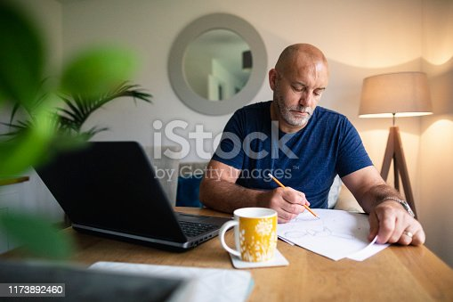 A shot of a mature man using a laptop and writing down notes on a piece of paper, he is wearing casual clothing.He is sketching a few designs