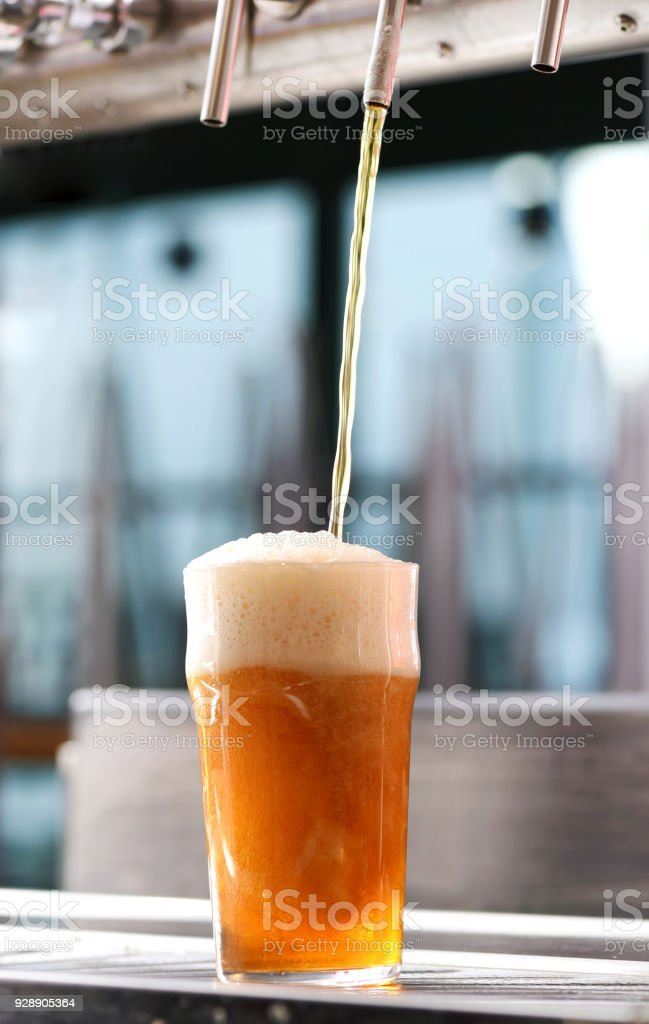 Drafting a glass of chilled draft beer stock photo