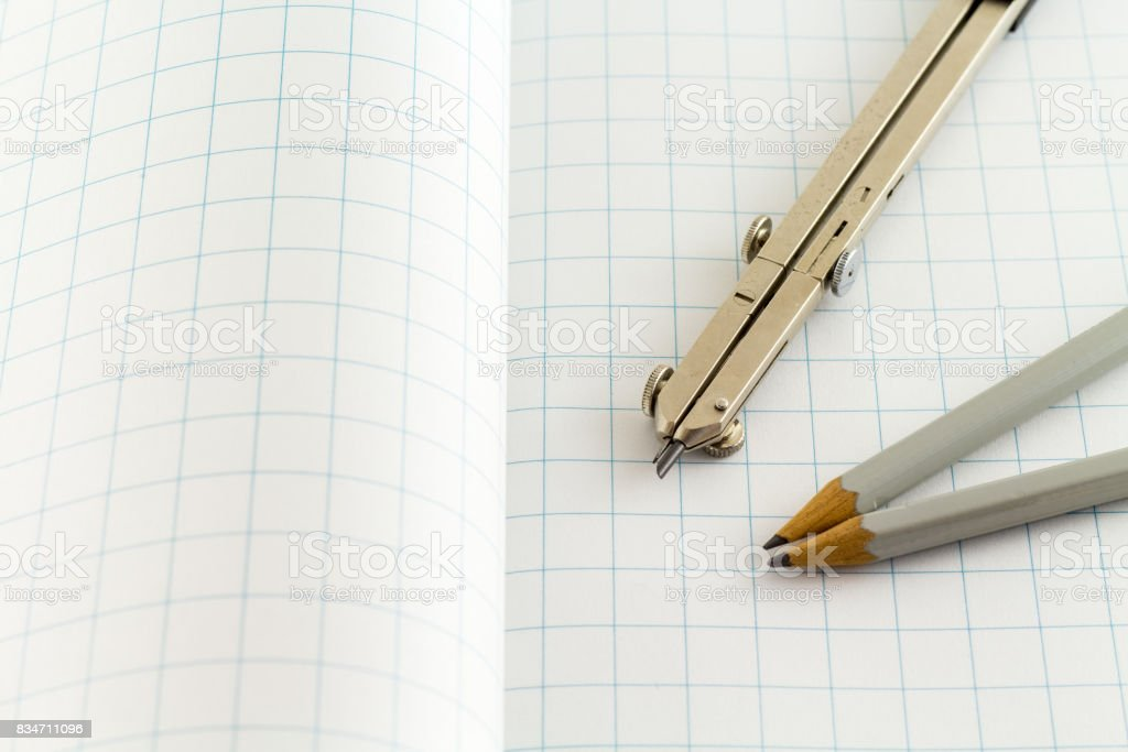 Drafting Compass And Pencil On Checkered Paper Stock Photo & More