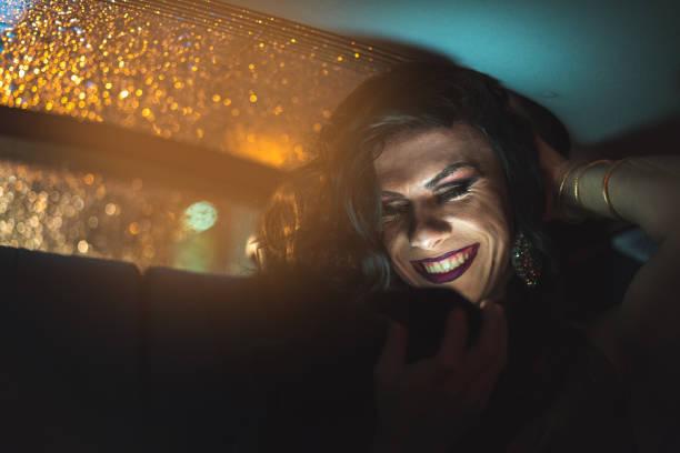 drag queen met behulp van mobiele op auto - drag queen stockfoto's en -beelden