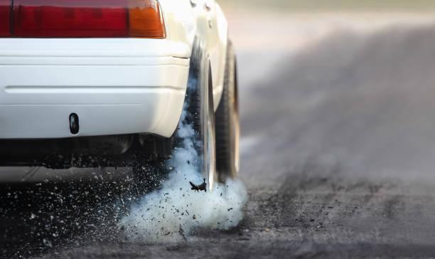 drag racing auto brennt kautschuk aus seiner reifen in vorbereitung auf das rennen - autoschleifen stock-fotos und bilder