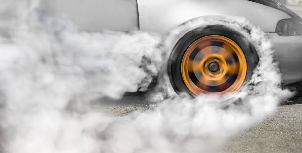 drag racing car burns rubber off its tires in preparation for the race - rubber stock photos and pictures