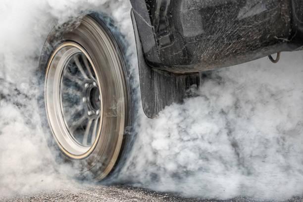 drag racing auto brennt kautschuk aus seiner reifen in vorbereitung auf das rennen - autosport stock-fotos und bilder