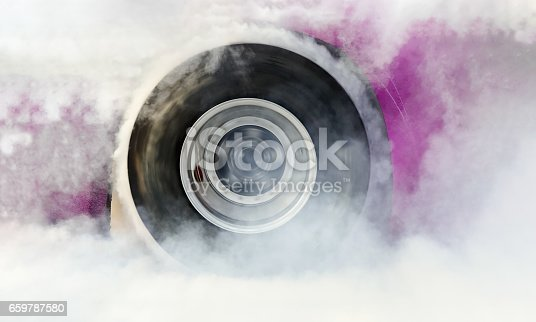 istock Drag racing car burns rubber off tire for the race 659787580